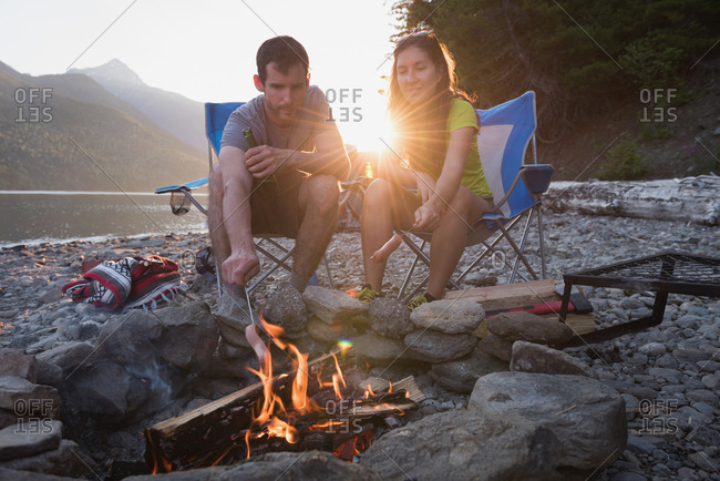 Couple roasting hot dog on campfire at countryside
