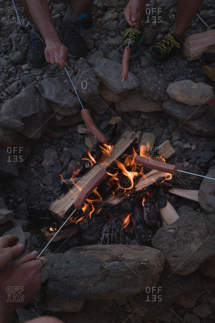 Group of friends roasting hot dogs on campfire at countryside