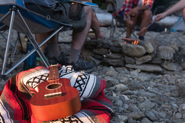 Close-up of guitar on picnic blanket at campsite