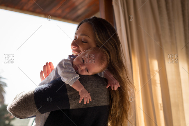 Happy mother holding her baby at home