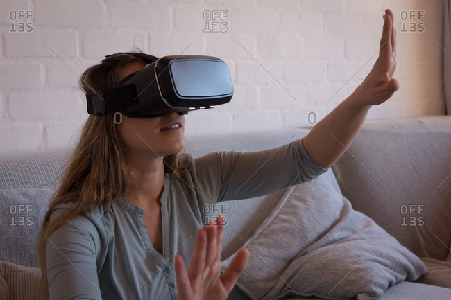Woman using virtual reality headset on sofa at home