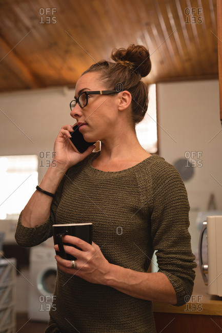 Close-up of woman with coffee cup talking on mobile phone at home