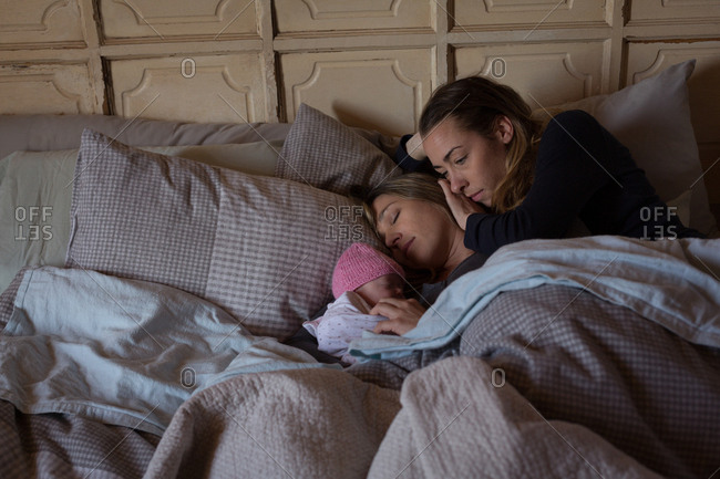 Lesbian couple with baby relaxing on bed at home