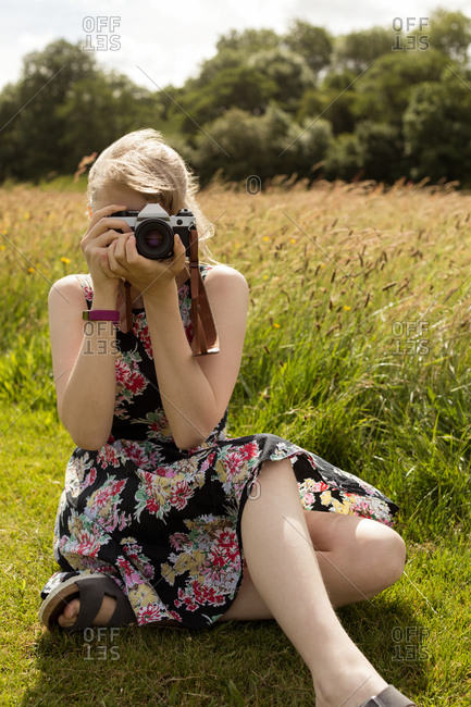 Woman clicking photo with digital camera in the field