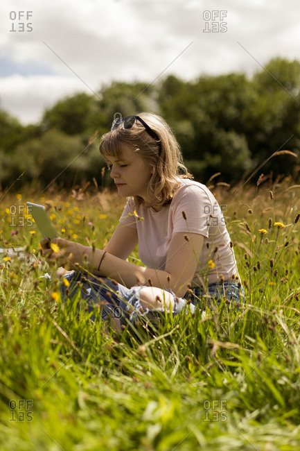 Young woman using digital tablet in the field