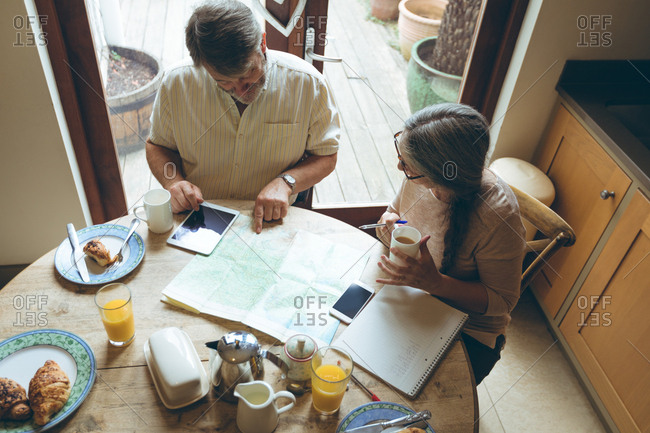 High angle view of senior couple discussing over a map at home