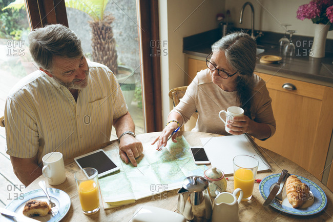 Senior couple discussing over a map at home