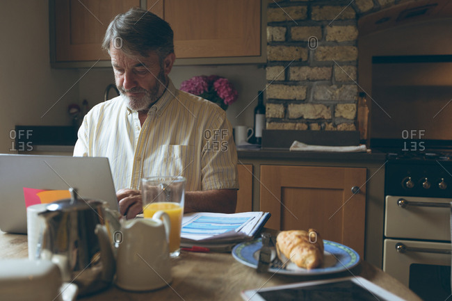 Senior man using digital tablet on dining tablet at home