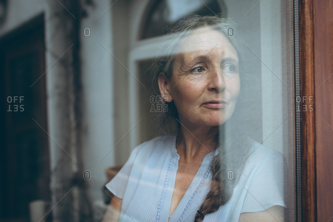 Thoughtful senior woman looking through window at home