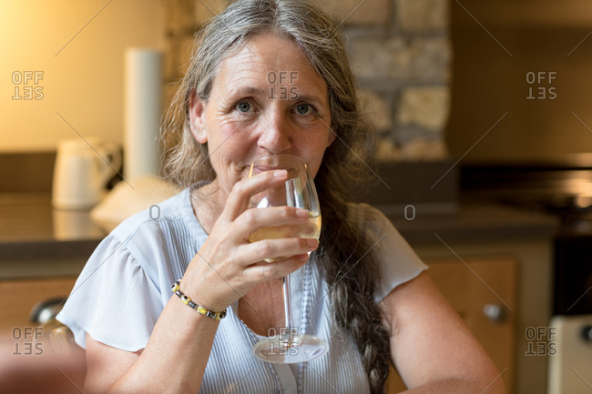 Portrait of senior woman having wine at home