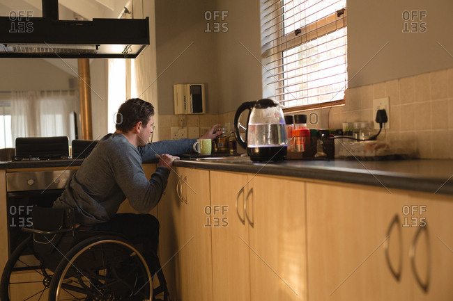 Disabled man preparing coffee in kitchen at home