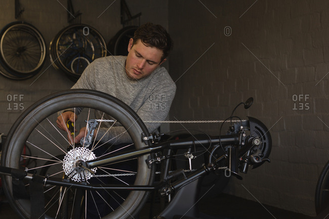 Young disabled man repairing wheelchair at workshop
