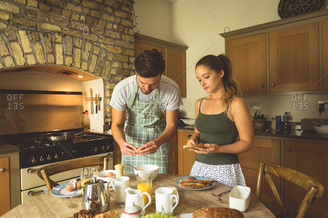 Couple preparing breakfast on dinning table at home