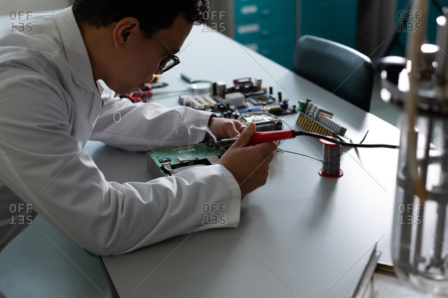 Male scientist experimenting on circuit board in laboratory