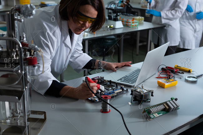 Female scientist soldering circuit board in laboratory