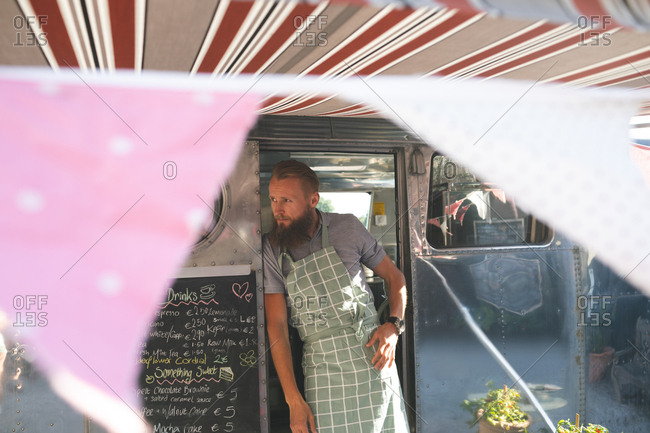 Thoughtful male waiter standing on food truck