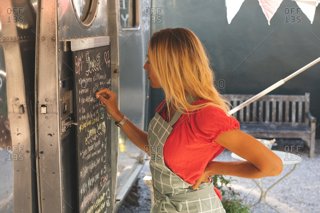 Side view of female waitress writing menu on menu board