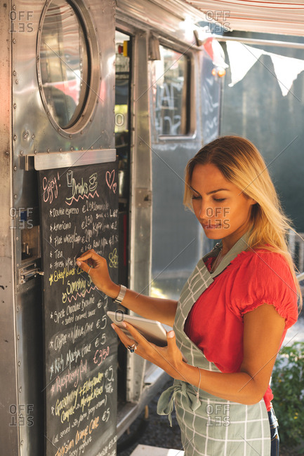 Beautiful female waitress writing menu on menu board while using digital tablet