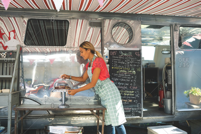Side view of female waitress working near food truck