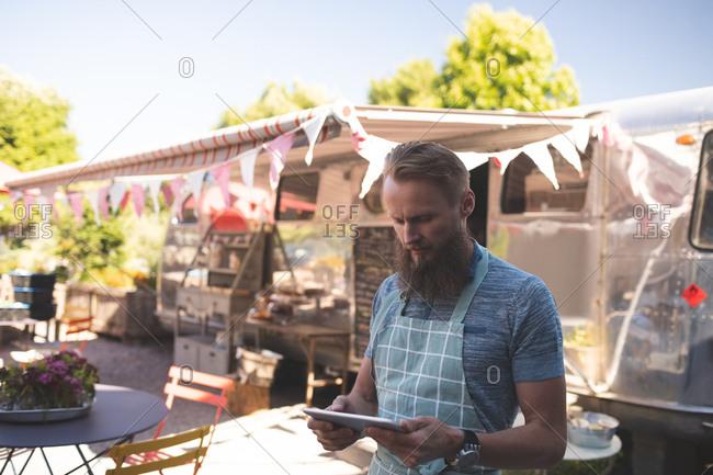 Attentive male waiter using digital tablet near food truck
