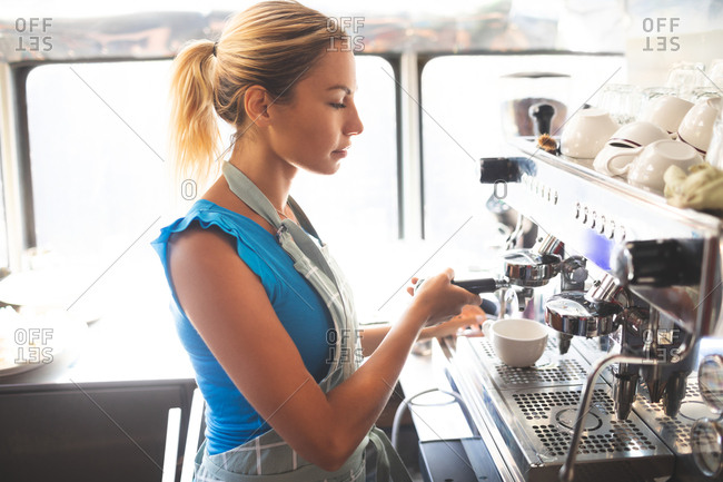 Woman waitress preparing coffee in food truck