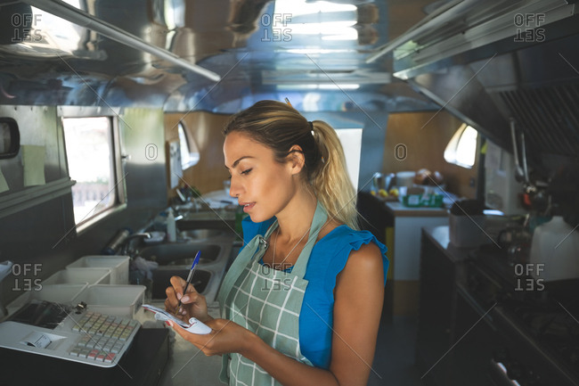 Woman waitress writing orders on notepad in food truck