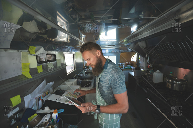 Waiter using digital tablet while operating billing machine in food truck