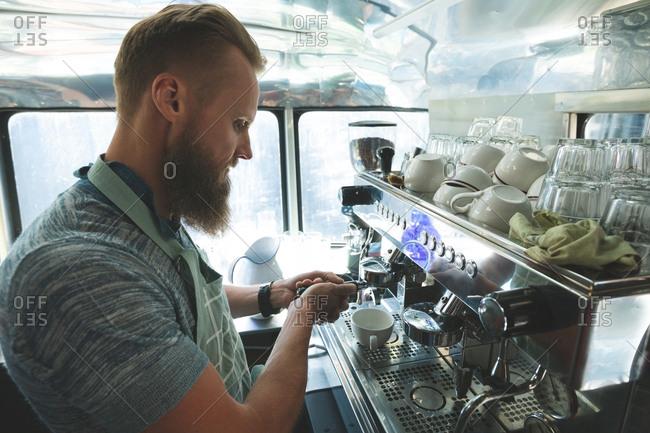 Side view of waiter preparing coffee in food truck