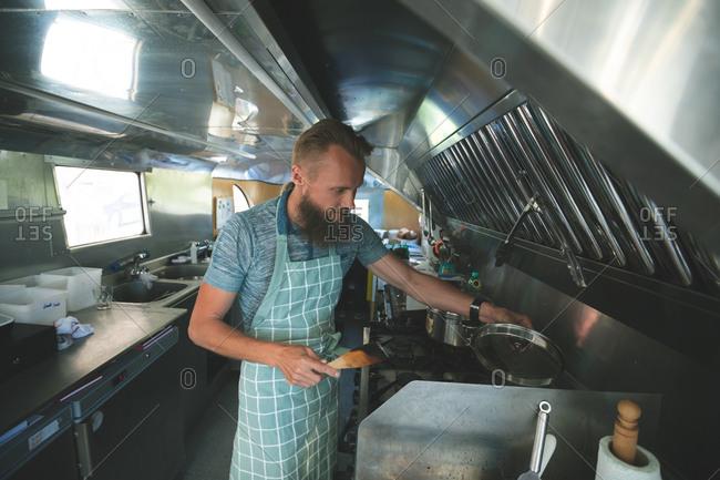 Handsome waiter preparing food in food truck