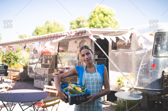 Female waitress holding vegetables in basket near food truck