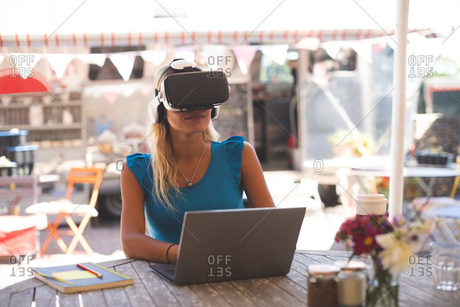 Woman using virtual reality headset with laptop in outdoor cafe