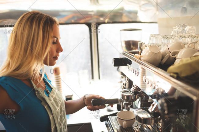 Side view of female waiter preparing coffee in food truck