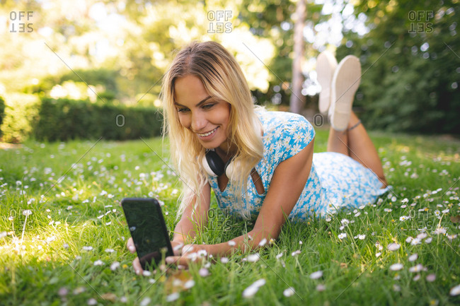 Woman taking selfie with mobile phone in the park