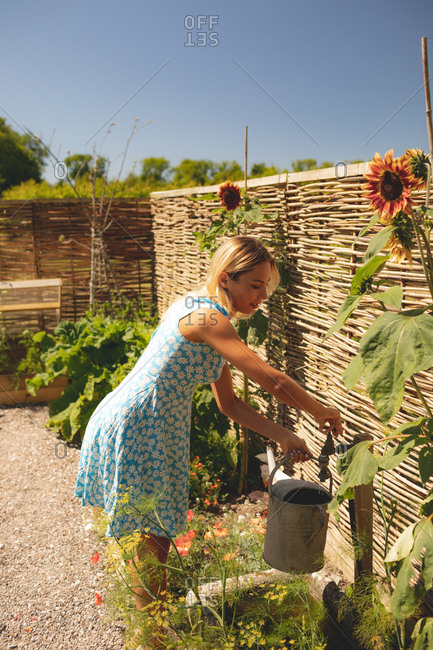 Woman filling water in the watering can at garden