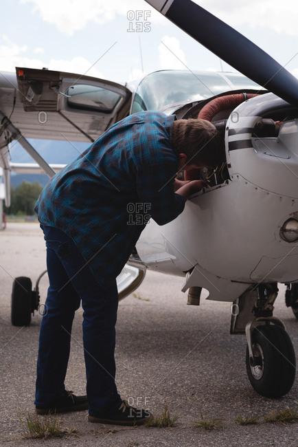 Engineer servicing aircraft engine near hangar on a sunny day