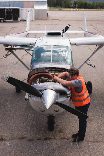High angle view of engineer servicing aircraft engine near hangar