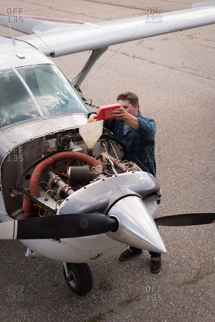 High angle view of engineer filling oil in aircraft engine