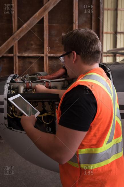 Mechanic using digital tablet while servicing aircraft engine at aerospace hangar