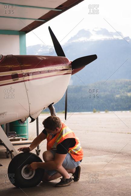 Mechanic servicing aircraft landing gear at aerospace hangar