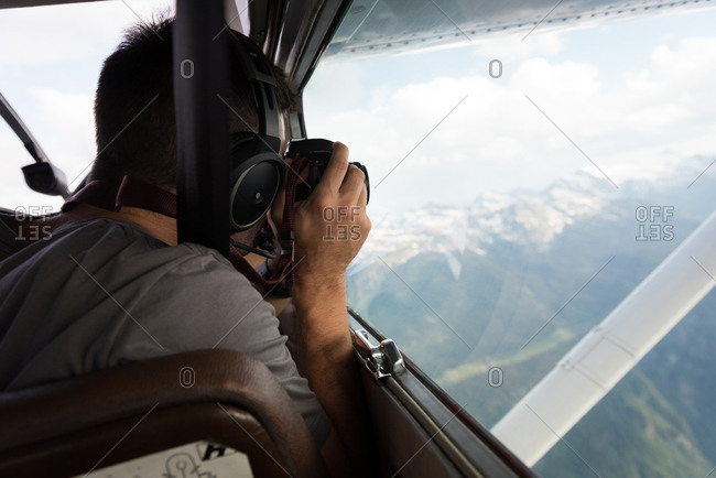 Pilot taking photos with camera while flying in aircraft cockpit