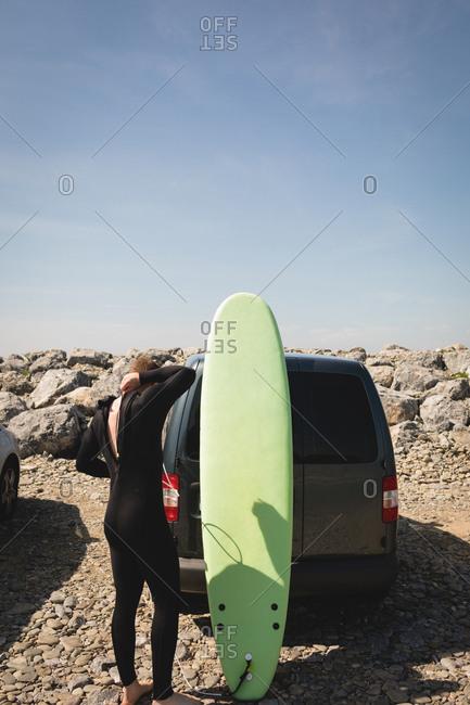 Rear view of surfer wearing wetsuit near beach