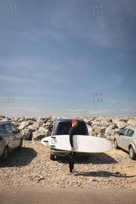 Surfer holding surfboard near beach on a sunny day