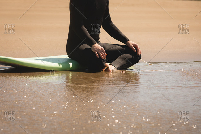 Low section of surfer sitting on surfboard at beach