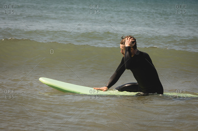 Surfer surfing on seawater on a sunny day