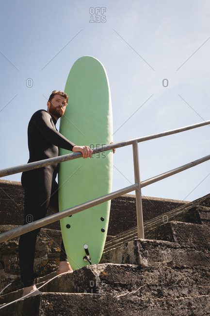Surfer with surfboard standing on staircase on a sunny day