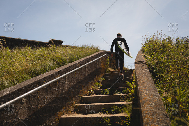 Low angle view of surfer with surfboard walking on staircase