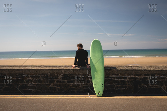 Rear view of surfer with surfboard sitting on surrounding wall