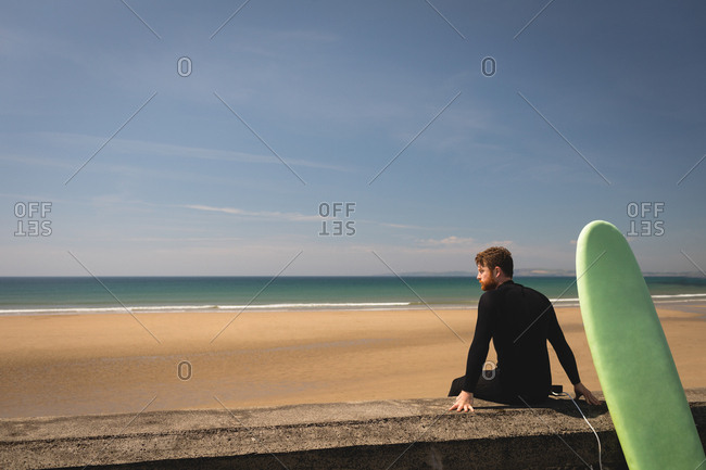 Side view of surfer with surfboard sitting on surrounding wall