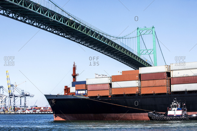 San Pedro, CA - June 28, 2018: Container ship passing under suspension bridge with assistance from a tugboat