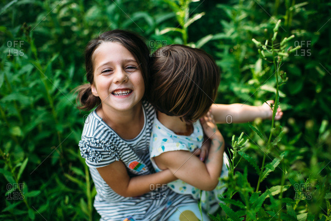 Little girl holding her younger sister in some weeds